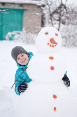 A boy and a snowman - a winter holiday