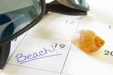 closeup of a calendar with Beach text with seashells
