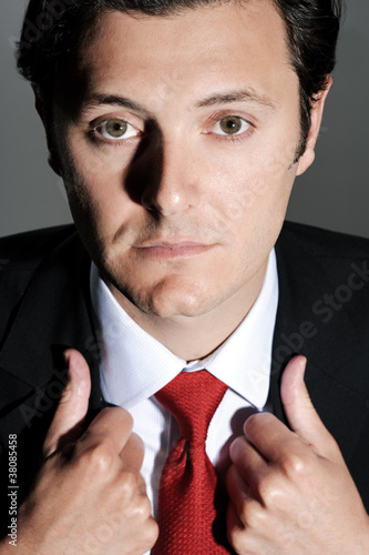 Businessman with a straight face adjusts his suit