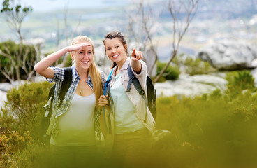 Two women pointing and looking ahead while hiking