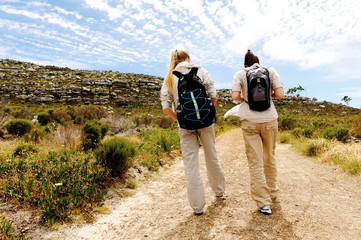 Backview of two young women hiking in nature