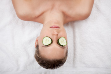 Woman with cucumber slices on her eyes at a spa