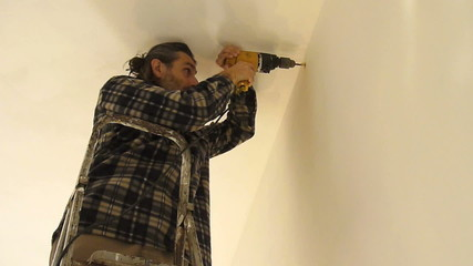 Man with power drill on ladder
