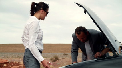 Business couple having fight by the broken car