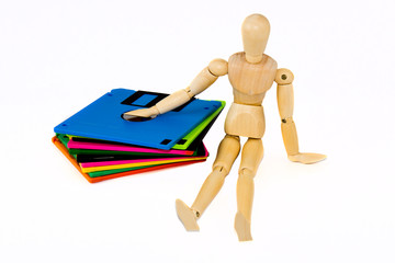 wooden manikin sitting near diskettes isolated