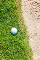 Golf Ball on the Grass Near Sand Bunker