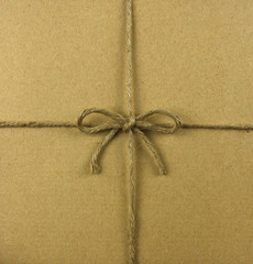 String tied in a bow, over brown recycled paper