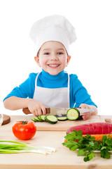 Little boy cutting the cucumber