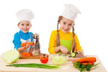 Two kids making salad