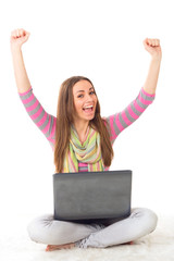 Happy female student with a laptop and arms up