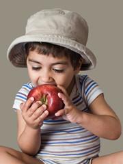 bambino che morde una mela rossa