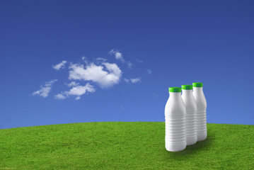 Three milk bottles on green grass against a blue sky