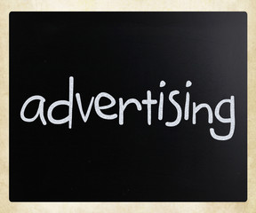 """The word """"advertising"""" handwritten with white chalk on a blackbo"""