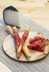 Appetizer with ham on breadstick and cheese slice