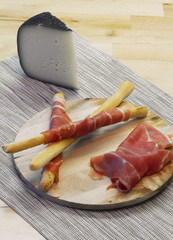 Appetizer with Parma ham on breadstick and cheese slice