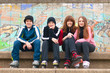 Group of happy teenagers sitting on the street in roller skate