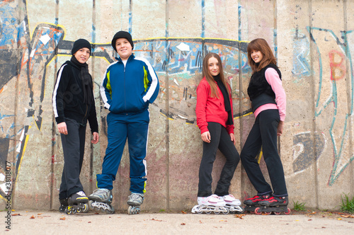 Group of teenagers going roller skating on cloudy autumn day
