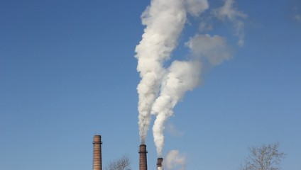 factory chimney with smoke under blue sky