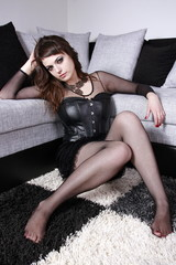 Gothic girl all in black leather in stockings
