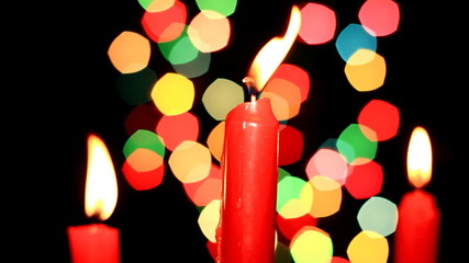 Three red candles on background of the color lights