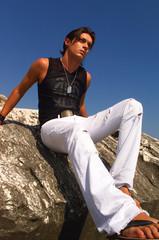 giovane uomo seduto sugli scogli