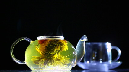 Transparent teapot with a flower inside and a cup.