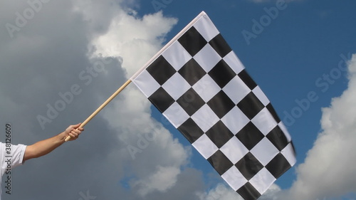 Hand holding a checkered flag on a raceway