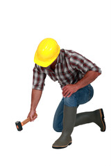 A manual worker with a hammer.