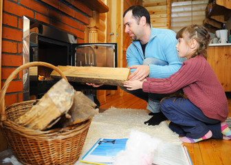 Father and daughter putting wood into fireplace