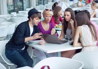 Cheerful friends browsing internet in a restaurant