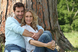 Couple sitting by tree