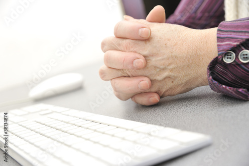 Hands of an old female near the keyboard