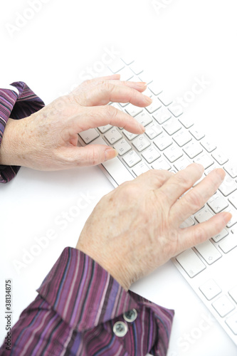 Hands of an old female typing on the keyboard