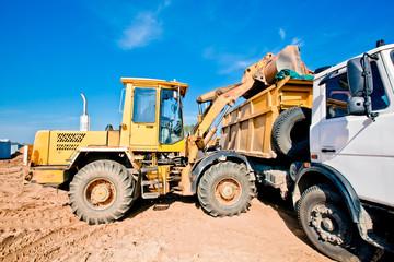Wheel loader machine loading soil into dumper truck tipper