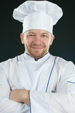 Positive chef in uniform with his arms crossed poster