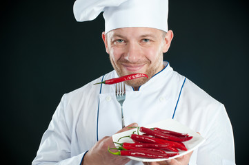 Chef in uniform with a plate of chili peppers smiling
