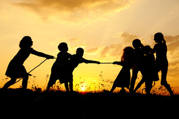 Silhouette, group of happy children playing , sunset, summertime