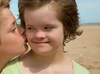 A boy kissing her sister with Down syndrome.