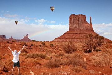 Enthusiastic tourists in Monument Valley and colorful balloons