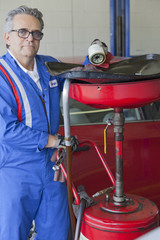 Portrait of senior mechanic standing besides car spray paint equipment