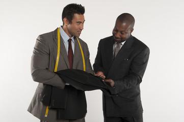 Tailor showing man a black suit