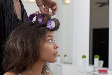 Young woman having hair curled in beauty salon