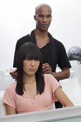 Asian woman sitting on chair with hairstylist standing behind