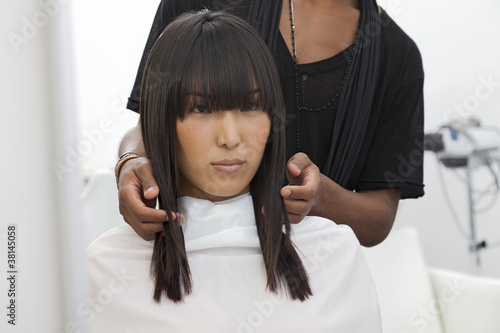 Asian woman getting a new haircut at beauty salon