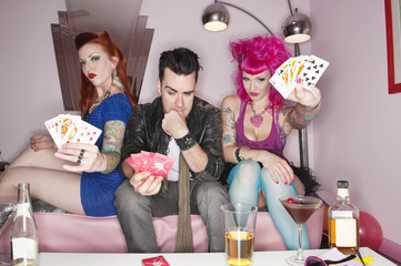 Portrait of females showing their playing cards while man thinking