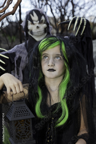 Little witch holding lantern with boy standing behind wearing grim reaper costume