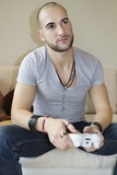 Casual young man playing video game