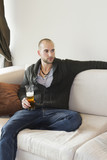 Young man sitting comfortably on sofa holding a drink
