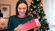 Young happy woman gets present, christmas tree in background
