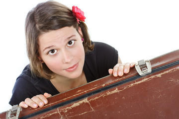 Attractive young woman looking from behind a suitcase